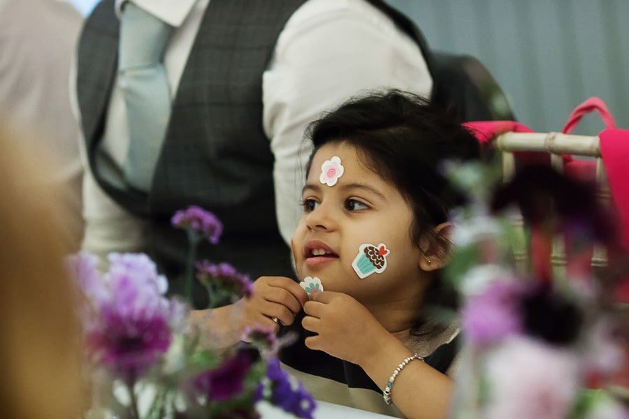 Girl with stickers on face at wedding dinner