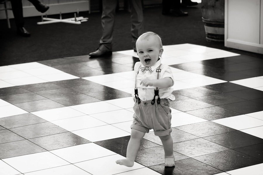 boy running across checked dancefloor