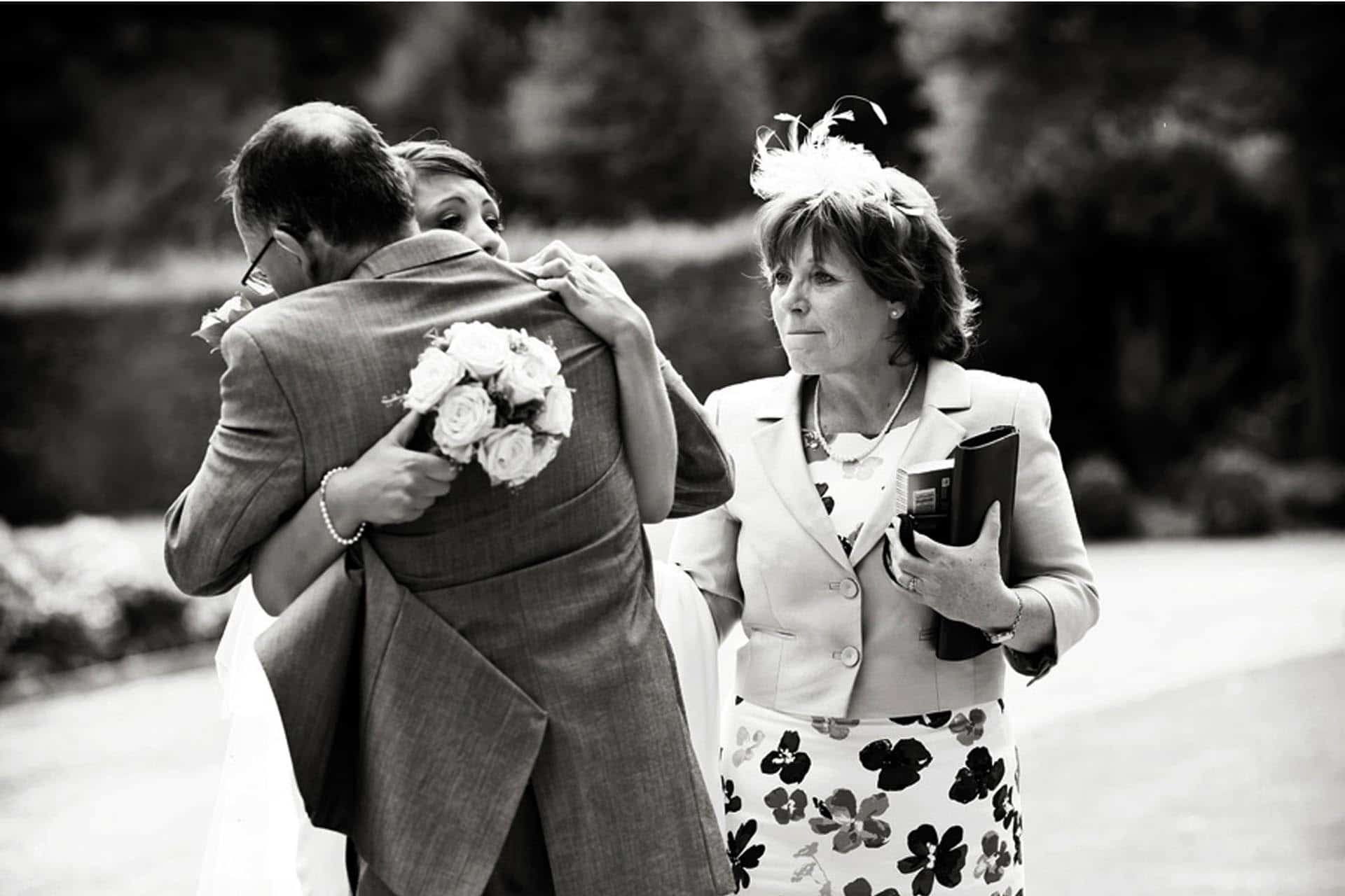 bride and father hugging mum crying