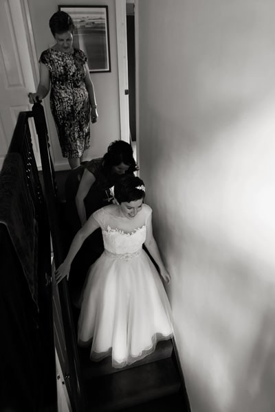 bride walking down stairs in dress with family behind