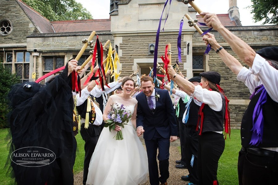 Bride and groom walking under Morris Dancers
