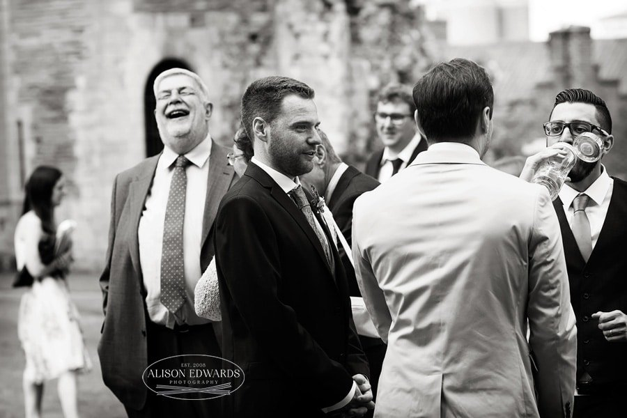 Man laughing amongst wedding guests