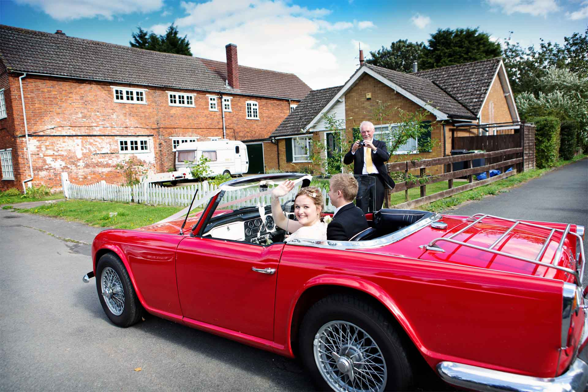 bride and groom leaving church in red car