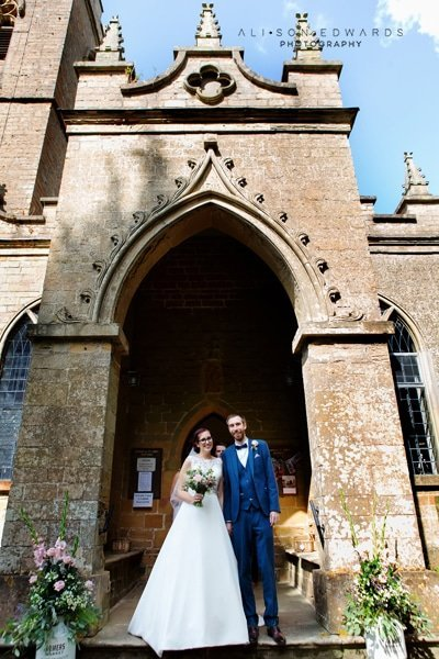 bride and groom outside of st james church papplewick