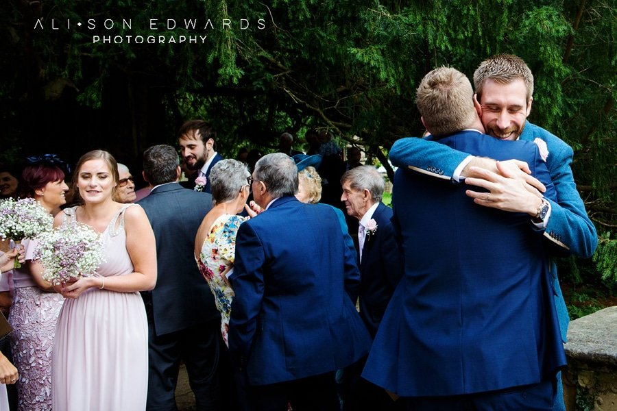 groom hugging guest at st james church papplewick