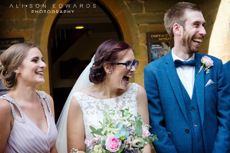 bride groom and bridesmaid laughing after ceremony at st james church papplewick