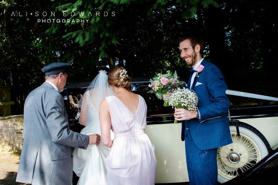 groom holding flowers while bride gets in wedding car at st james church papplewick