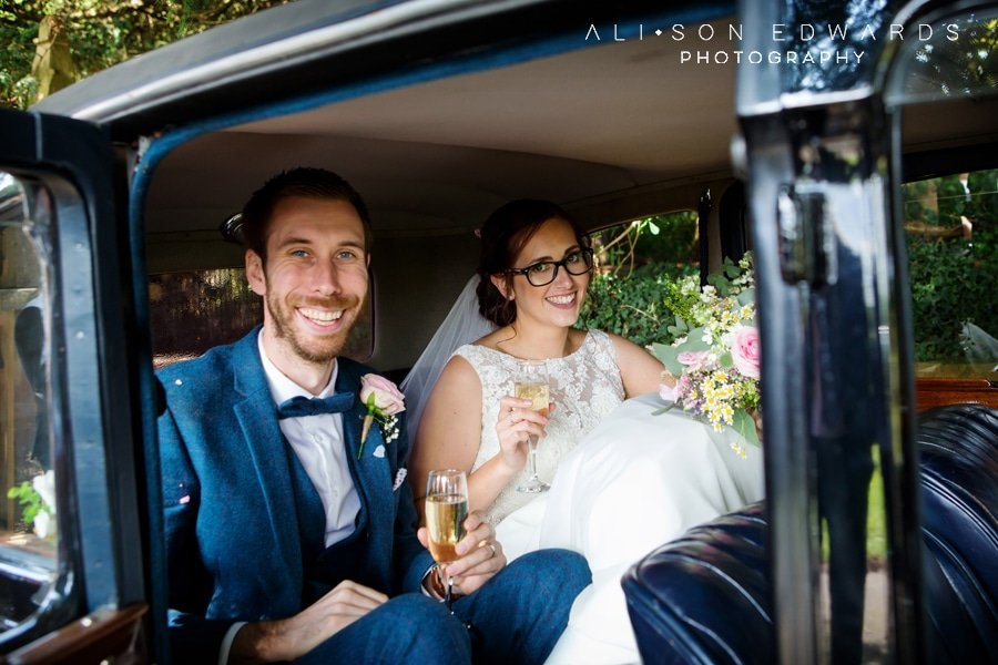 bride and groom in wedding car at st james church papplewick