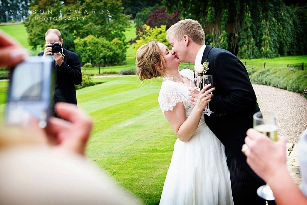 guest taking photo of bride and groom kissing