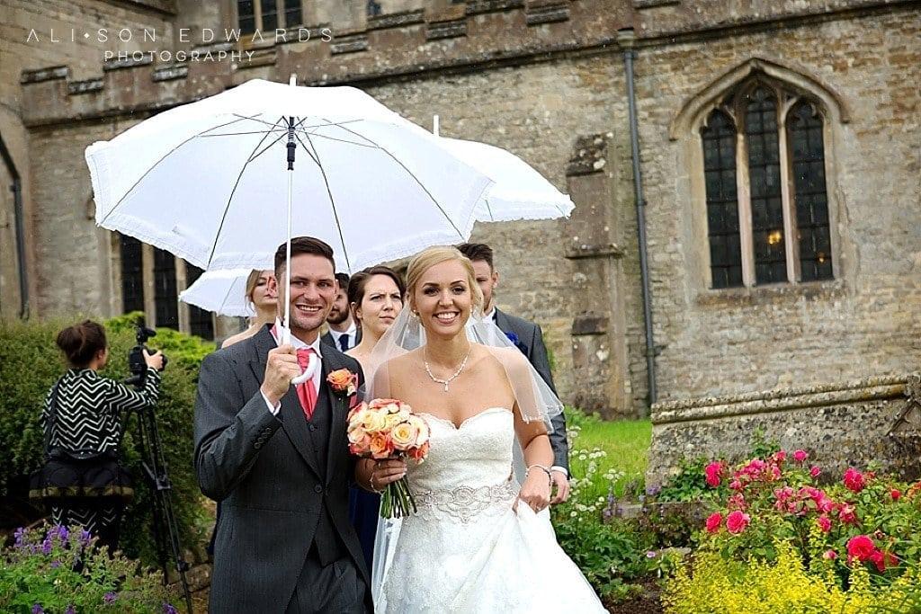 bride and groom leaving church in rain