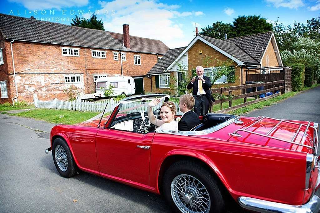 Bride and groom leaving church in red sports car
