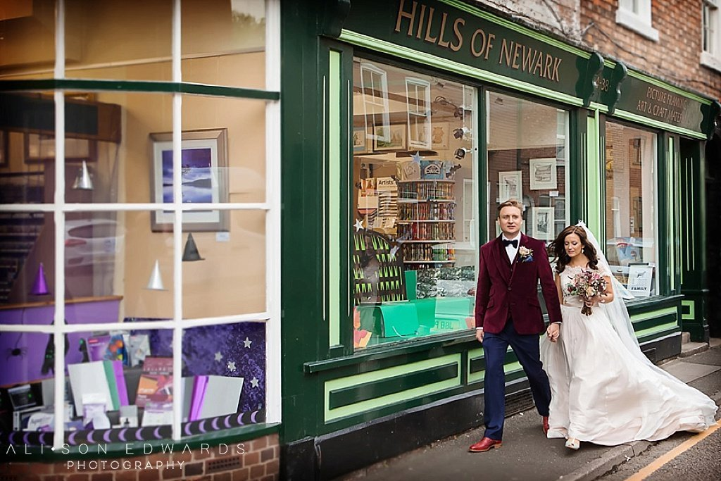 bride and groom walking past book shop in newark dont like posing photography