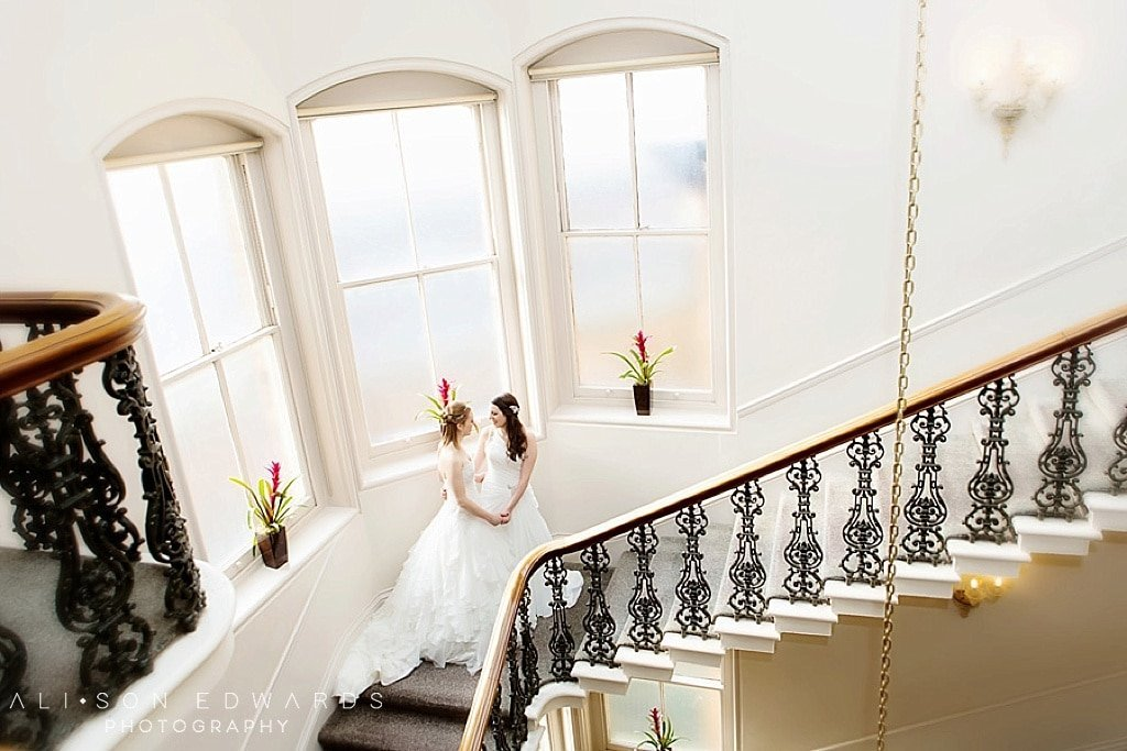 two brides holding hands on staircase at York hotel