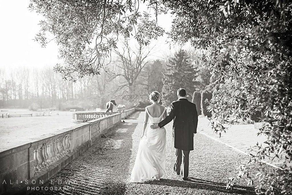 bride and groom walking away under summer trees