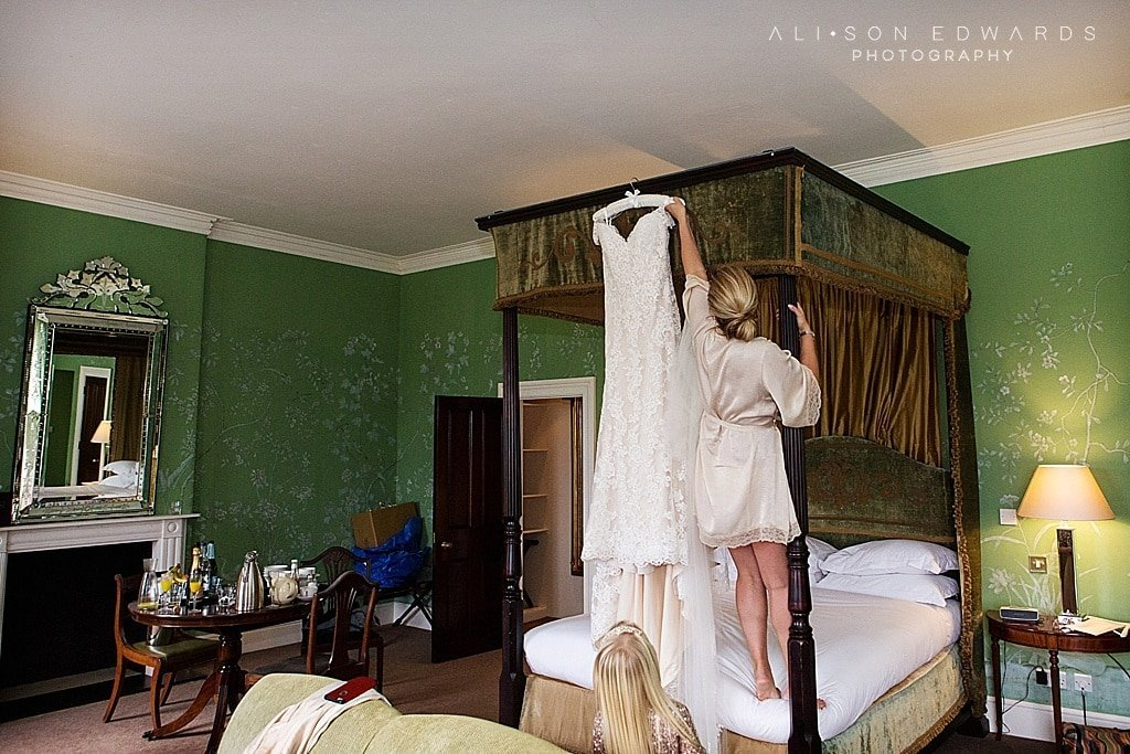 bride standing on bed to get wedding dress