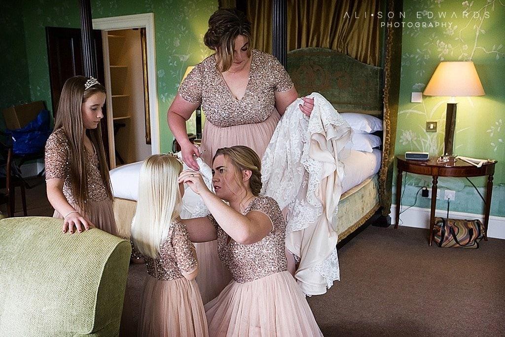 bridesmaid putting tiara on flower girl