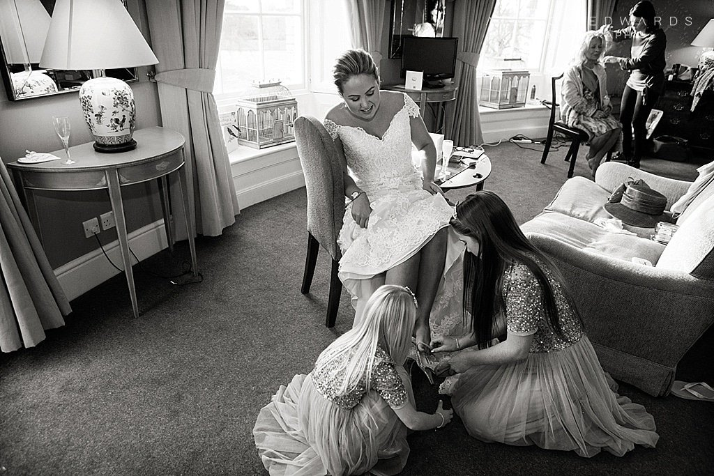 bridesmaids putting shoes on bride at Stubton Hall