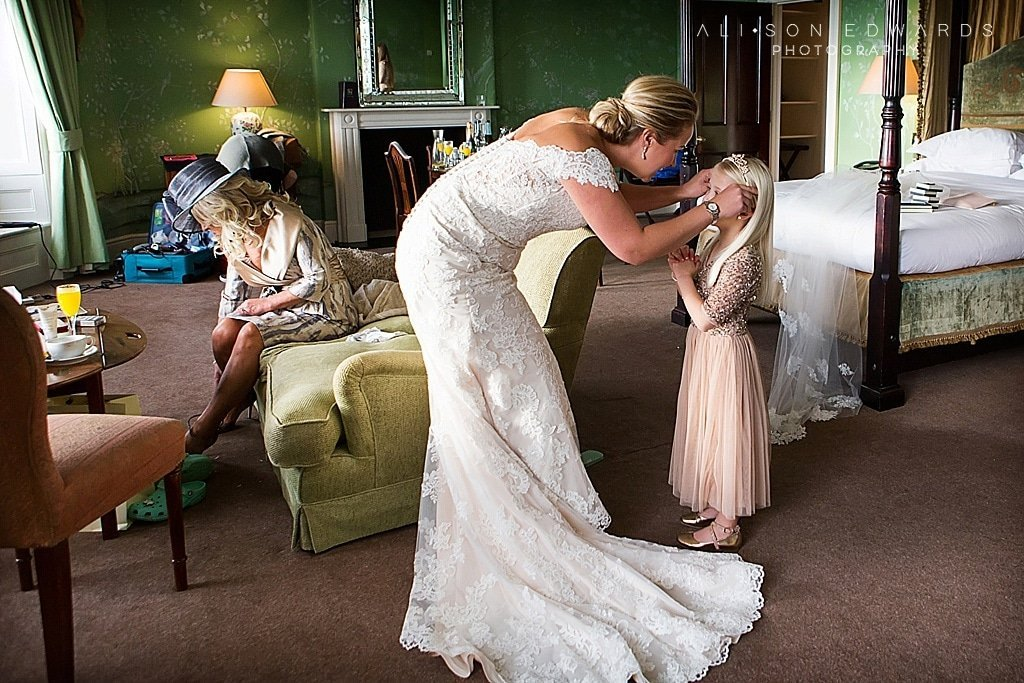 bride putting flower girl's tiara on