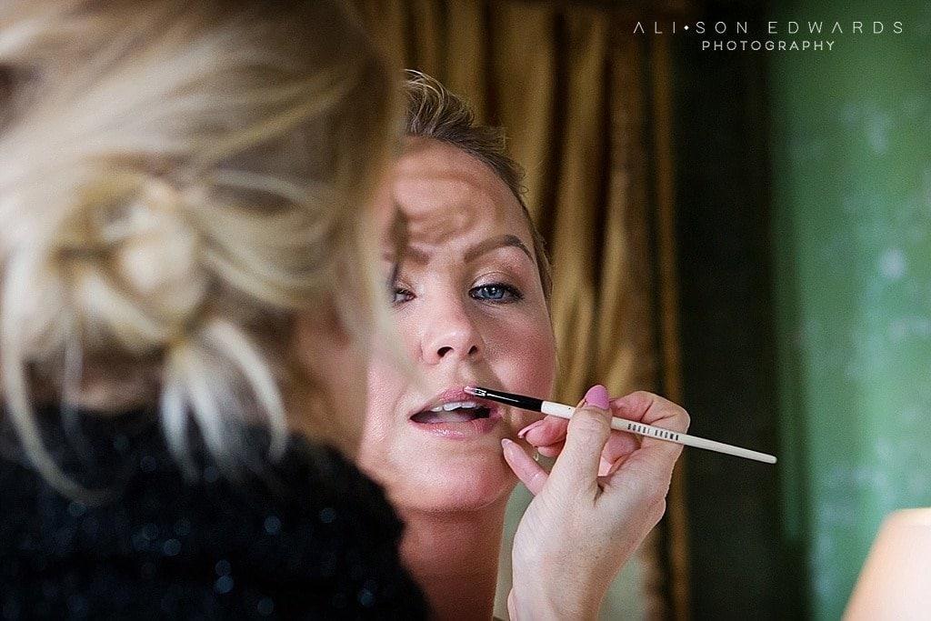 make up artist putting lipstick on bride