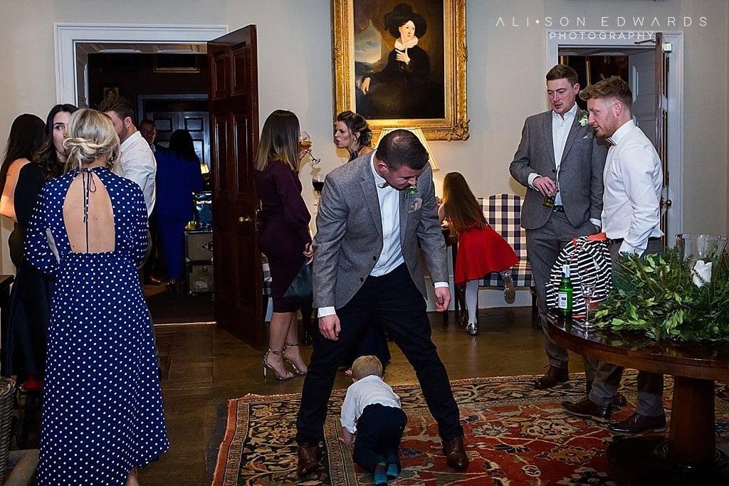 boy running through dad's legs at stubton hall wedding