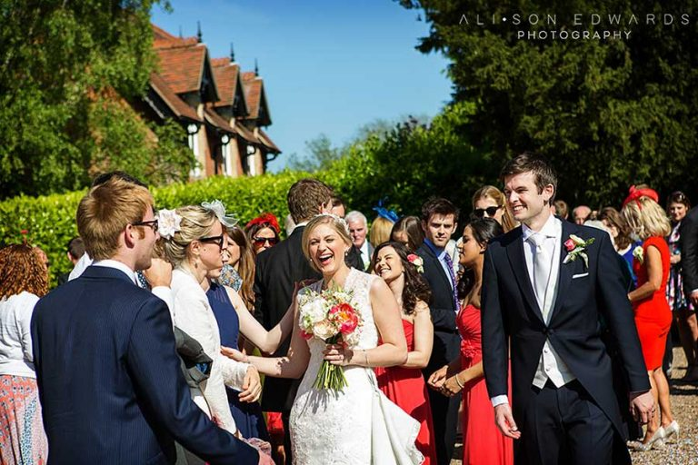 bride and groom with guests outside of Eakring church captured by Nottingham wedding photographer