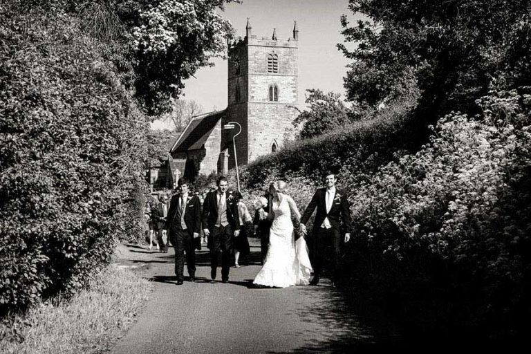 bride and groom walking up church lane with wedding guests in Nottinghamshire