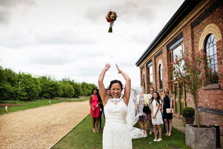 Nottingham wedding photographer captures bride throwing bouquet at Carriage Hall