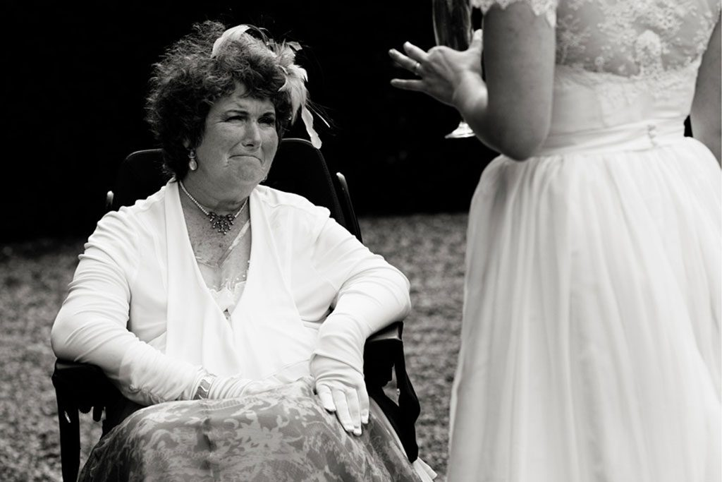 lady in wheelchair looking at bride lovingly