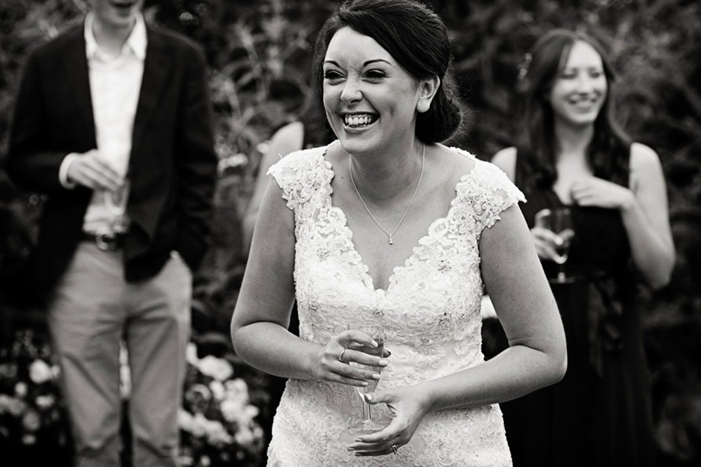 bride laughing at speeches at hambleton hall