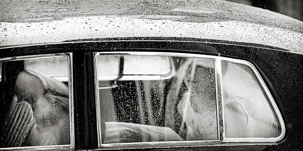 wedding photography of bride arriving at church on a rain day
