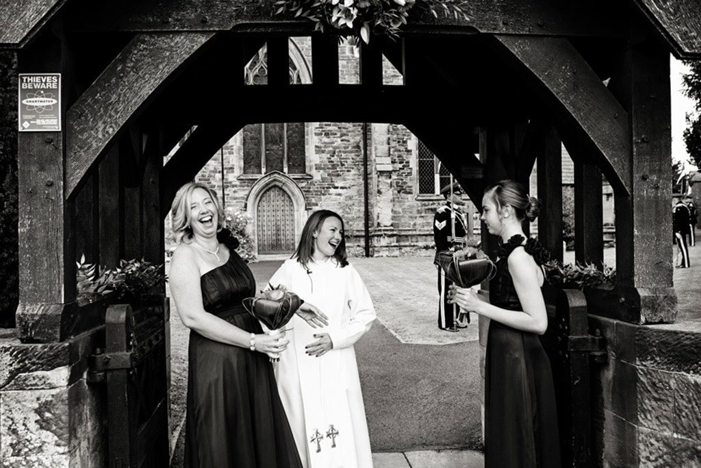 bridesmaids laughing with vicar outside of Leicestershire church