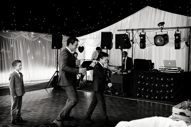 man dancing with two children laughing at marquee wedding