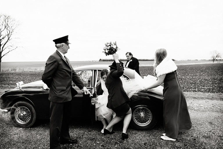 bride getting out of car on a windy day