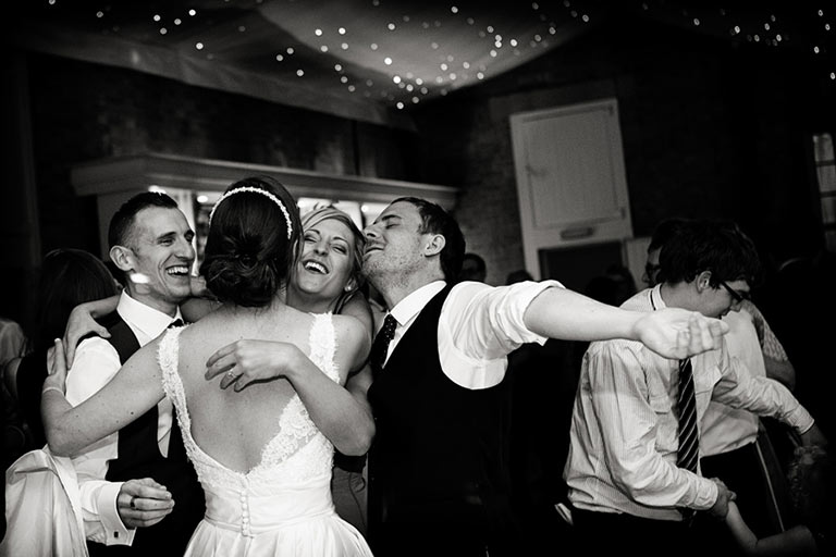 bride and groom dancing and hugging guests at Norwood Park wedding photography