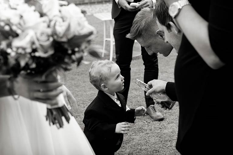 man pretending to give young boy a drink at wedding