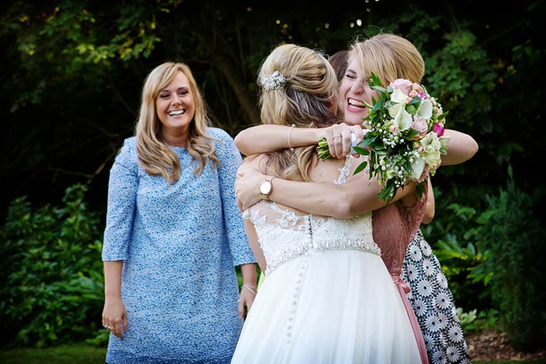 bride and friend hugging catching bouquet at old vicarage