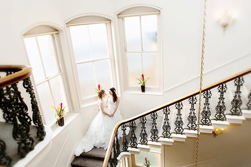 two brides holding hands on stairs at York Hotel