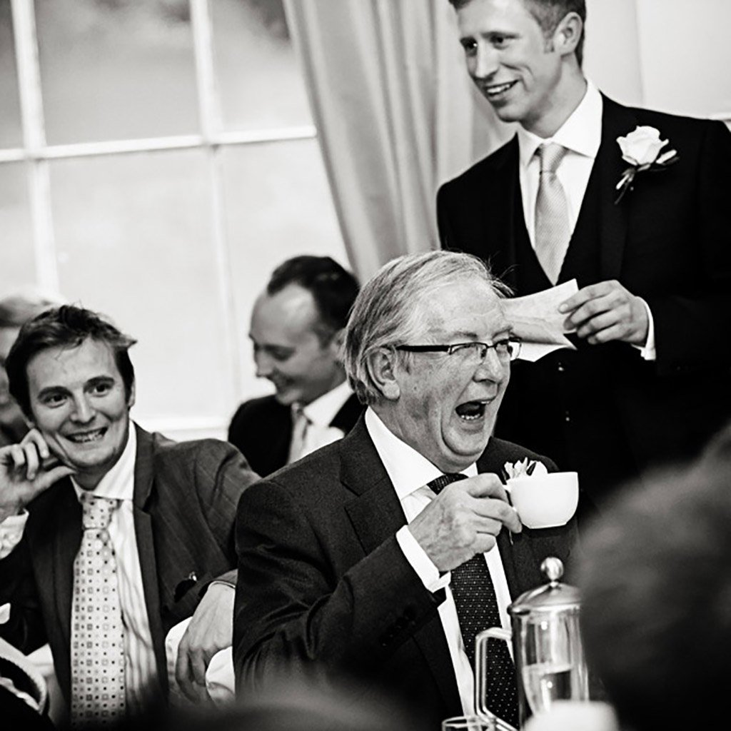 bride's father laughing with cup of tea at Prestwold Hall