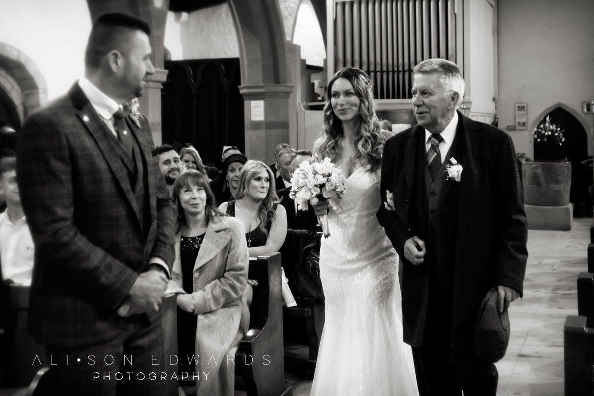 groom smiling at bride walking into draycott church wedding