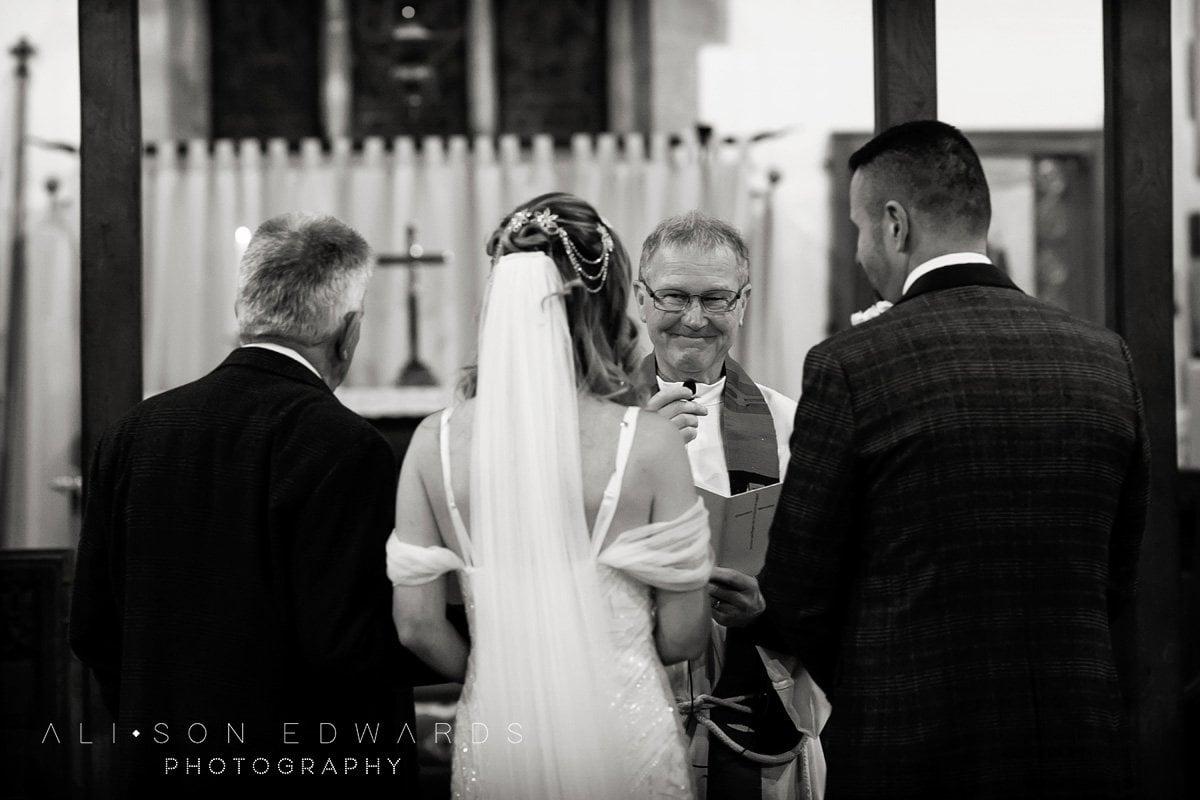 vicar smiling at bride and groom