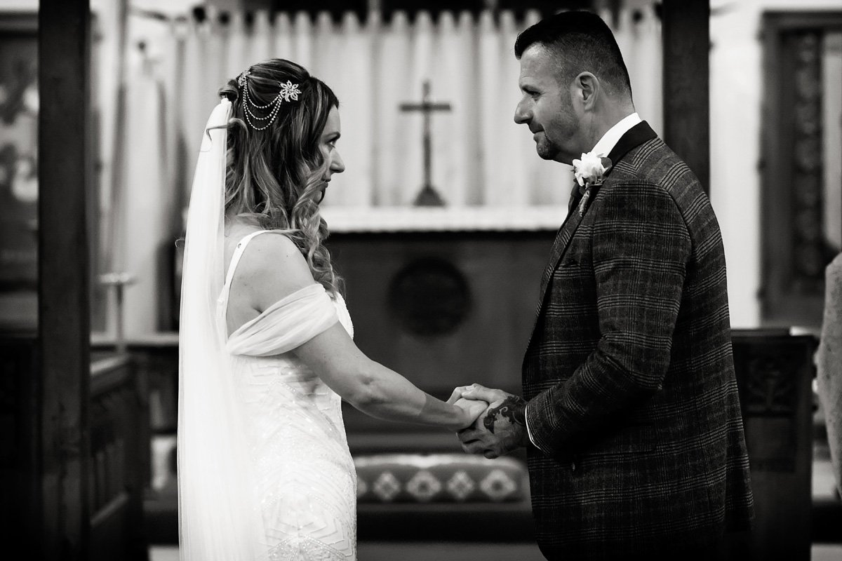 bride and groom looking lovingly in church