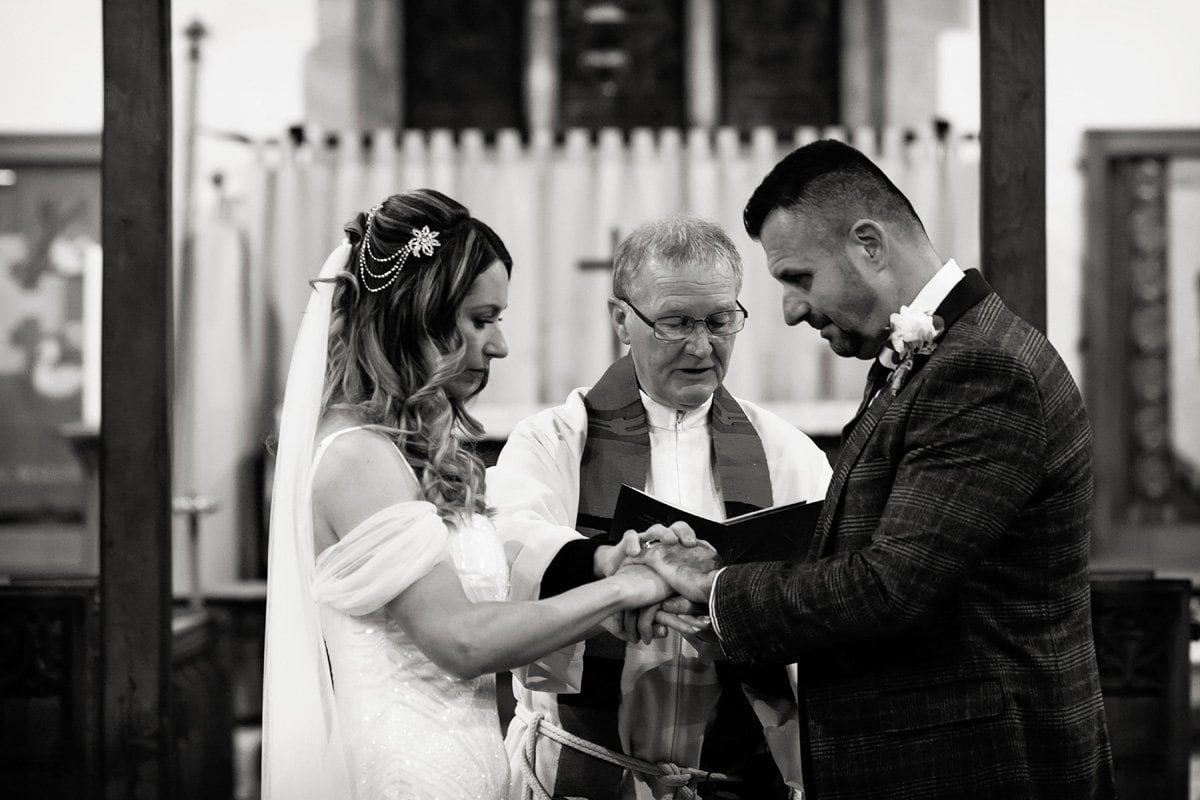 vicar blessing rings in draycott church wedding
