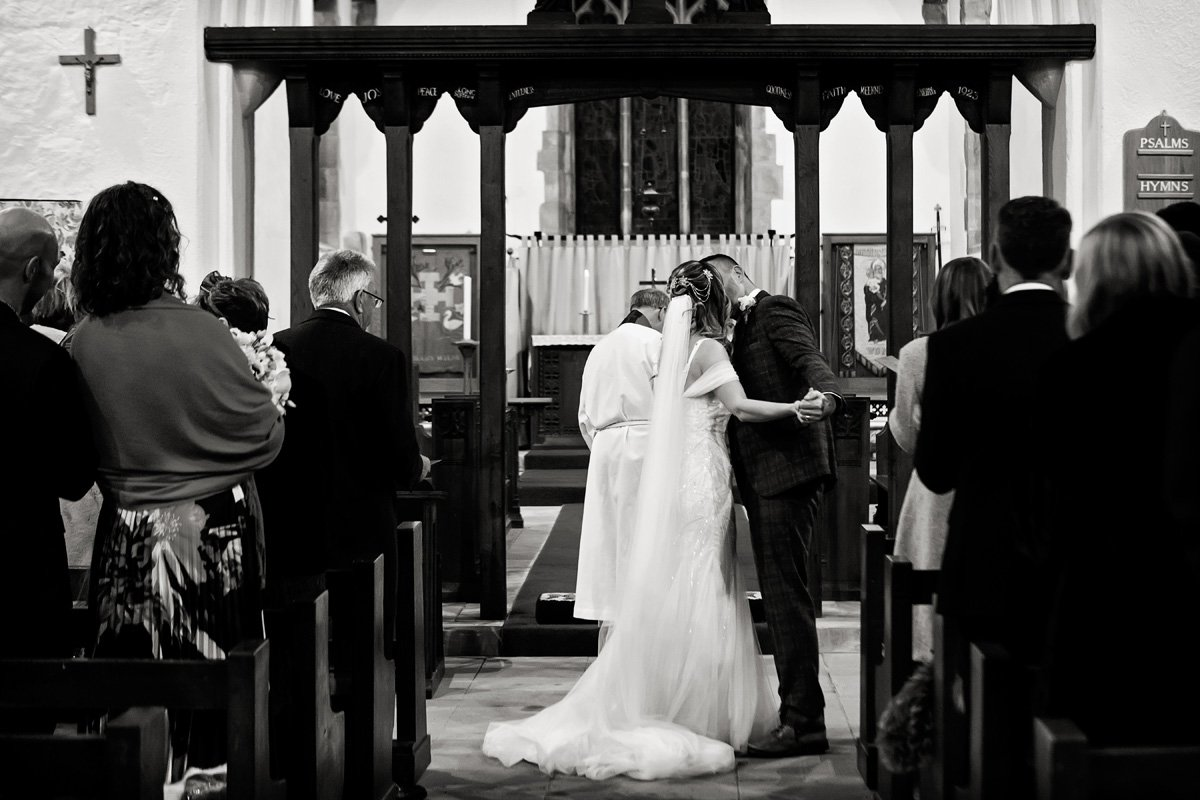 bride and groom's first kiss in draycott church wedding