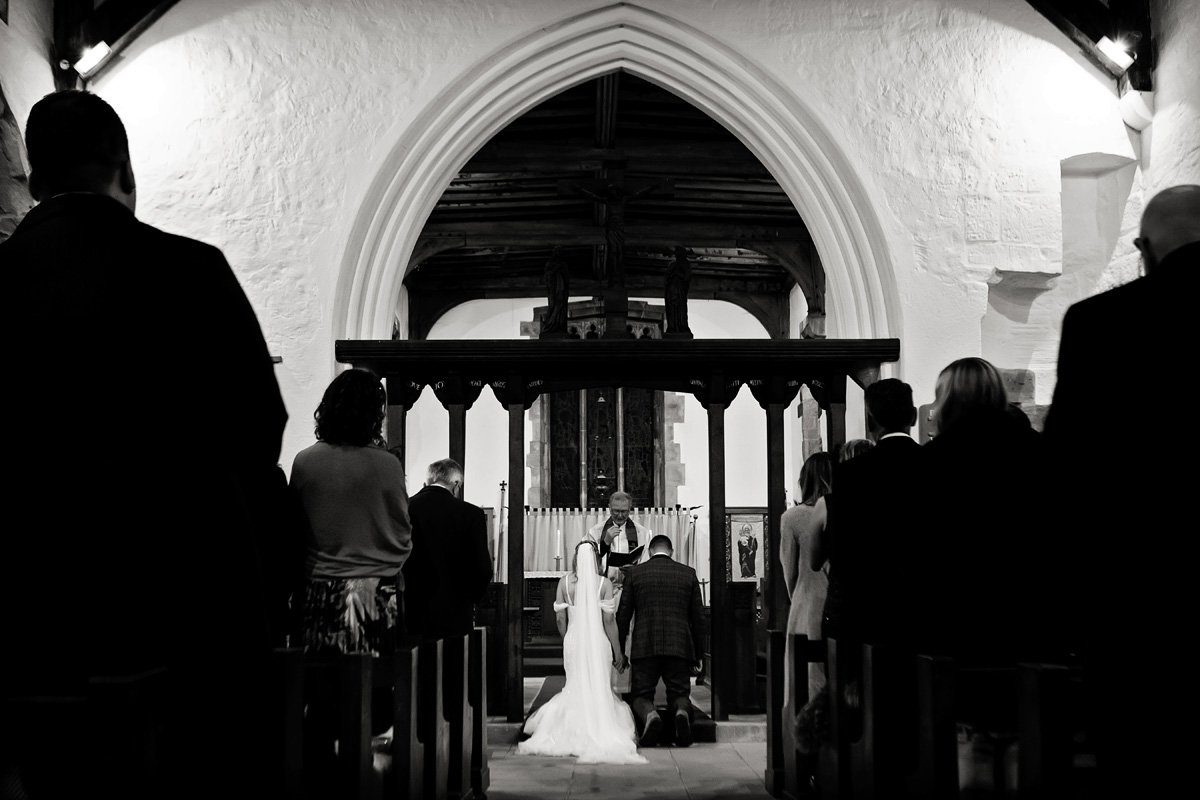 bride and groom kneeling at alter in church