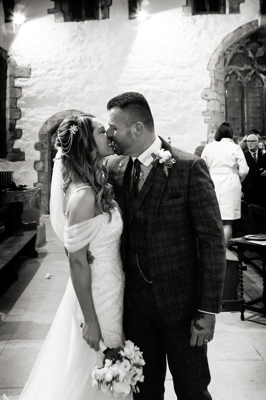 bride and groom kissing in church entrance