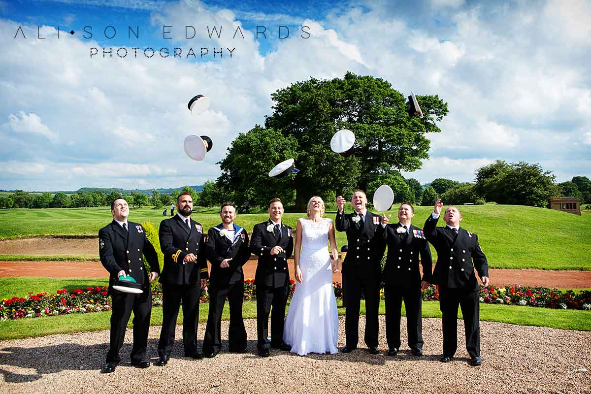 bride and groom at The Nottinghamshire with navy groomsmen throwing hats in air