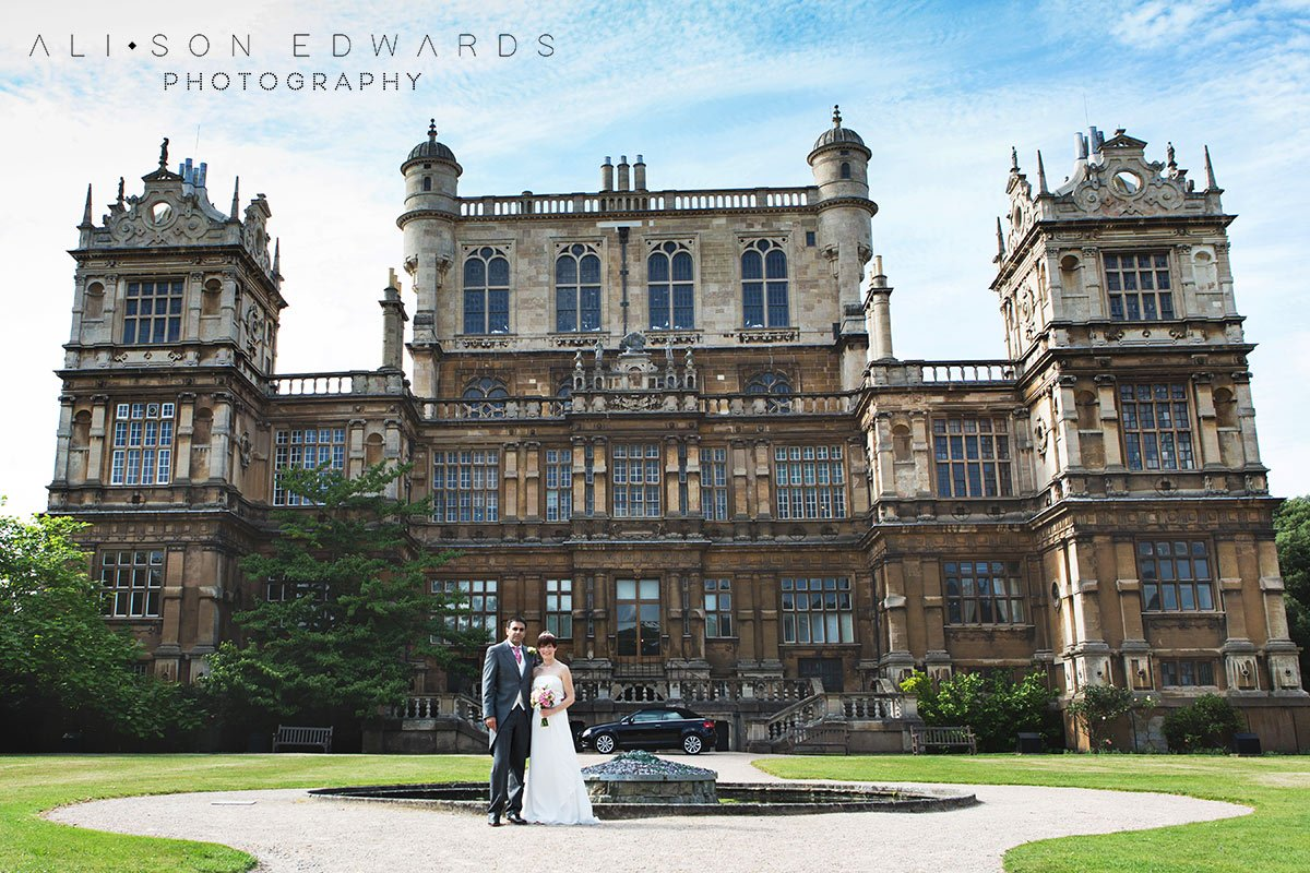 bride and groom in front of wollaton hall