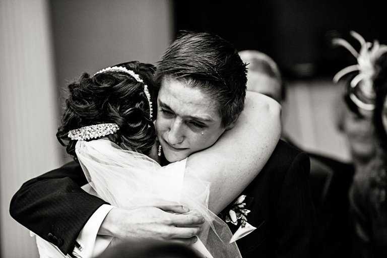 intimate wedding photography of boy hugging bride
