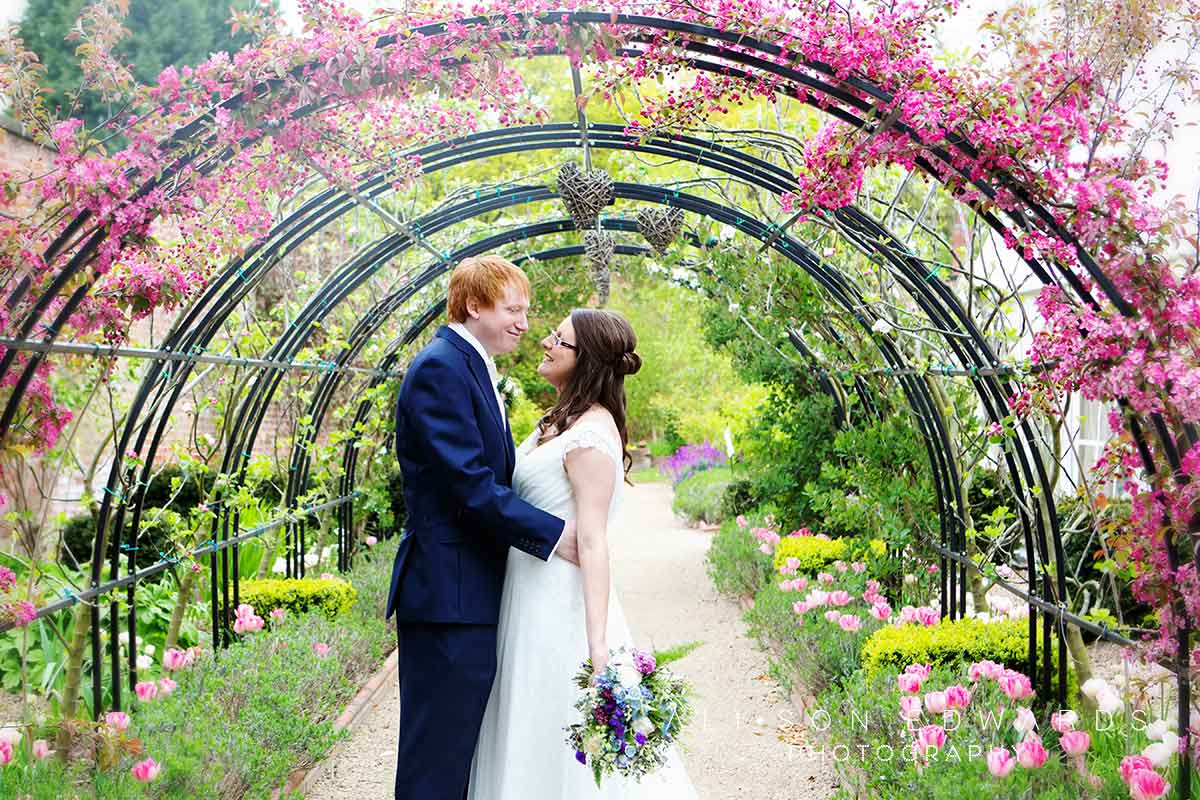 bride and groom under pretty floral archway the walled gardens