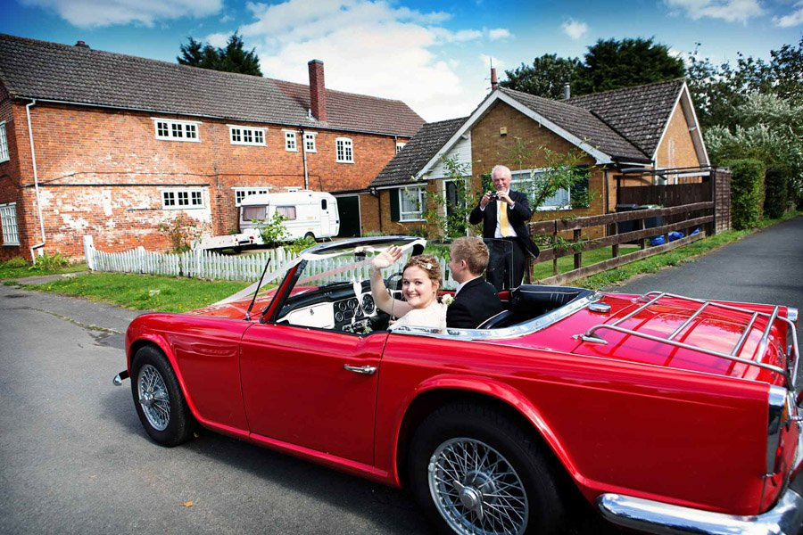 bride and groom leaving church in sports car Nottingham wedding photographer